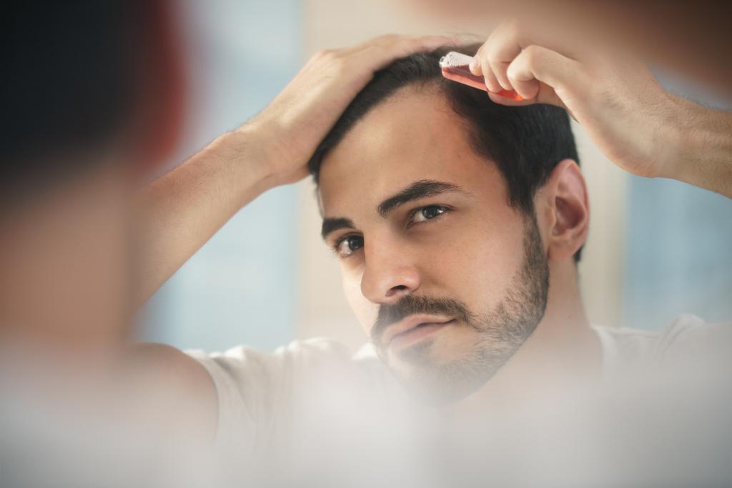 hombre aplicando producto para la caida del cabello